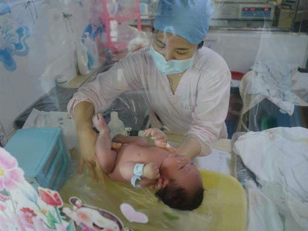 """8点,病区所有医护人员在护士站进行医护集体交班后,夜班护士与A班护士需到床边对每个新生儿进行详细的交接班。护士朱水燕分管在足月区病情相对稳定的病人,夜班护士在床边一一汇报新生儿昨天具体病情、治疗、检查、用药、吃奶等情况,她仔细查看新生儿全身皮肤、管道、呼吸情况、脐部情况、护理记录及治疗记录等,了解新生儿具体的病情变化,并在心中迅速对新生儿病情做出一个初步判断,制定当班的护理计划及确定护理重点:13床新生儿吃奶时间中血氧会下降,停止喂奶后血氧可迅速回升,喂奶时需注意分段喂养,注意血氧变化情况;20床新生儿肛周皮肤轻度潮红,提醒管床医生开鞣酸软膏外涂;25床新生儿今天光疗第三天,皮肤黄染已经减退,预计今天可以停光疗,需提前预热好温箱…… 目前病区的新生儿共有20多位,朱水燕负责其中的8位。8:30交接完结束,朱水燕马上开始今天的第一项工作:新生儿沐浴。沐浴是新生儿极其享受的时刻,有时有些新生儿会哭闹,护士们就会轻轻哼着歌曲安抚新生儿。每个新生儿沐浴完毕后,朱水燕护士会根据新生儿的具体情况及需求给予新生儿抚触、脐部护理、臀部护理、口腔护理等。为了尽量减少对新生儿的刺激,对每个新生儿采用集中护理,沐浴完后都立刻完成其各项治疗:雾化吸入、清理呼吸道、更换到期的胃管等,全程下来,每个新生儿至少需要花费15~20分钟时间。工作三年来,朱水燕给无数新生儿洗过澡,而她自己还没当过妈妈,她笑称面对病区里的新生儿自己已经提前进入母亲角色了。 在完成沐浴与治疗的同时,对于病情变化较大的病人,她还要参与医生查房,介绍新生儿当前的基本情况,了解医生对新生儿病情的分析,当天治疗的变化,以便调整自己的护理措施。她说参与医生查房能学到很多知识,是年轻护士成长的很好的学习方式,所以无论再忙都会坚持跟随医生查房。医生查房开始后,医嘱也在不断的出来,不时有医生过来对朱水燕说""""25床急抽血""""、""""15床新开了补液""""……面对着这些纷繁而至的工作,朱水燕一点也没有慌乱,她笑着说每日都是这般的,工作虽然多,但也有轻重缓急,做好安排,先完成紧急重要的工作,其他的可缓一缓迟点再完成。"""