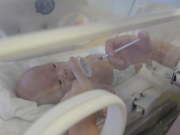 """19床宝宝是2月14日就住进病区的""""老居民"""",护士长称他为老人家。由于他住了三个多月,和每一位姑娘都非常熟络,也被姑娘们娇惯坏了,饿了的时候如果没有及时喂,就挥舞小手蹬着小腿哇哇大哭抗议。这是个27周的早产儿,还不到七个月就着急地从妈妈肚子里出来了,因出生时情况很差,有创的呼吸机上了一个多月,无创呼吸机也用了快1个月,现在终于过了各种关卡。由于使用时间比较久,他的鼻子变成了""""朝天鼻"""",姑娘们有时会和他开玩笑,说他来自星星的宝宝。但是护士长护短,每每听到都会软语怼回,""""长得多帅,一点都不像外星人""""。其实停了呼吸机后,宝宝的鼻子会慢慢变回原来的模样。喂奶喂到一半的时候,新生儿唇周出现轻微发绀,血氧降至88%,原来是这个猴急的孩子光顾着吃,没想到要换气,大脑协调不了,血氧就往下掉。朱水燕立刻停止喂奶,把他扶起来拍背,血氧正常了再继续喂。"""