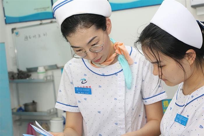 """迄今为止,罗立兰在护士的岗位上已经做了14年,谈到从学校毕业后做护士初尝滋味,辛苦之外,感受到更多的是温馨和成就。第一次被患者报以微笑、第一次在路上被患者认出、热情招呼……罗立兰说:""""那些患者温暖微笑的脸庞,我到现在都记得。"""",这也是她这14年来在压力重负下还始终在坚守在护士岗位的最大动力。图为罗立兰耐心给护士核对药物。"""