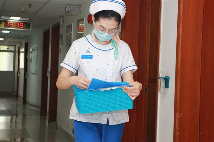"""""""做护士久了,人淡定了很多"""",罗立兰说,刚做护士的时候,""""玻璃心""""很脆弱,每当遇到困难就想逃跑、就想放弃。随着年纪的增长,感受到身上的责任越来越重,也更加淡然、洒脱,面对压力也能自我调节。罗立兰不单是工作中的""""女强人"""",心中也住着一位""""文青"""",不喜喧哗,喜欢安静地宅在家里看书,《傲慢与偏见》、《飘》……这些文学名著是她工作之外的另一种精神寄托。图为罗立兰为患者分发当天的口服药。"""